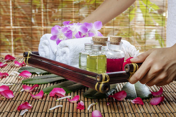 woman present spa essentials on wooden tray