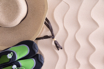 Boys beach hat and shoes on golden sand