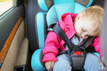 The little girl is sleeping in the car seat