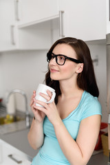 entspannte frau in ihrer küche mit einer tasse kaffee