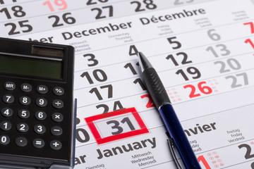 Kalenderblatt mit Stift und Rechner