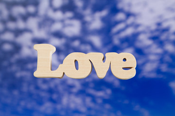 Love wooden letters on sky background