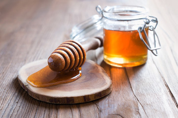 Honey in jur with wooden dipper