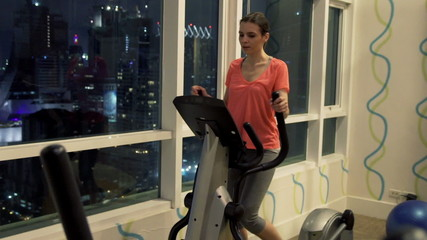 Young woman exercising on elliptical machine in the gym at night