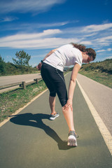 Athletic woman suffering pain in leg calf by cramp