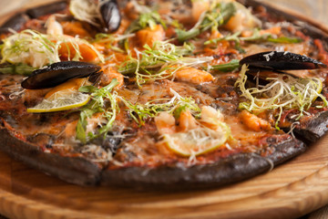 "Italian pizza ""Di Mare"" with black dough and seafood on wooden t"