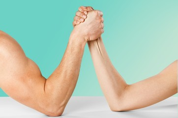 Adult. A man and woman with hands clasped arm wrestling