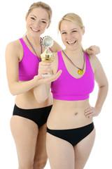 Frauen in Sportbekleidung mit Pokal und Medaille
