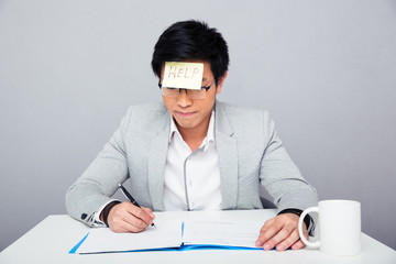 Businessman sitting at the table with adhesive note