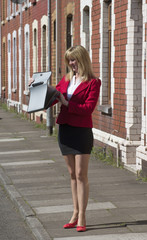 Businesswoman carrying briefcase along a residential street