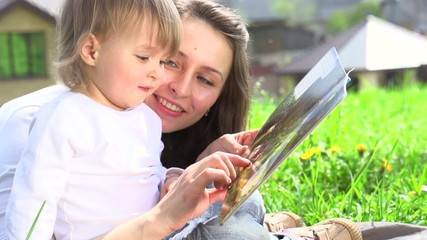 Mother with her baby reading the book outdoors. Slow-mo 240 fps