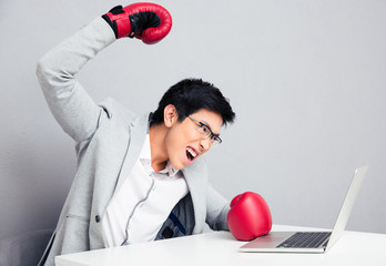 Angry businessman sitting at the table in boxing gloves