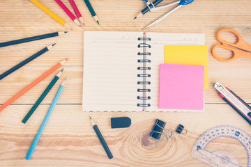 Notebook paper and school or office tools on wood table for back