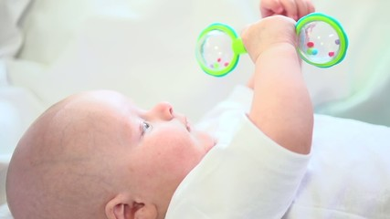 Baby boy playing with a rattle toy. Slow motion 240 fps