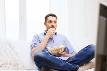 young man watching tv and eating popcorn at home