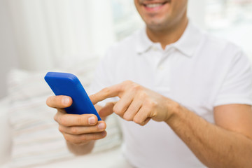close up of happy man with smartphone at home