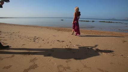 blonde sad girl in bright dress walks along beach