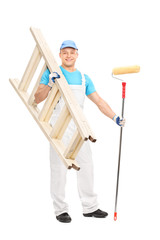 Young painter holding paint roller and a ladder
