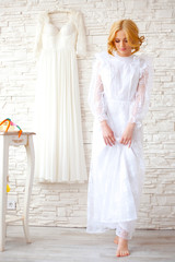 Beautiful blond bride near white brick wall