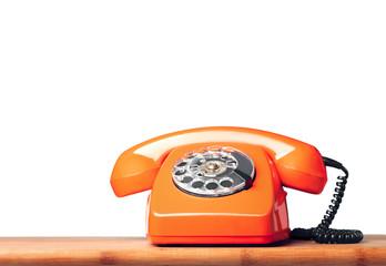 Vintage orange phone on the table Isolated on white