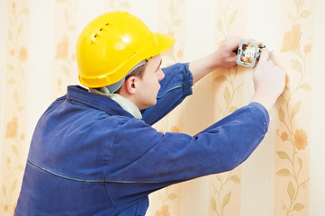 electrician at wall outlet installation