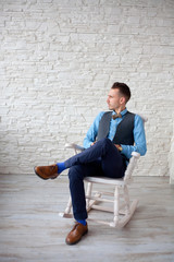stylish attractive man sitting in a chair