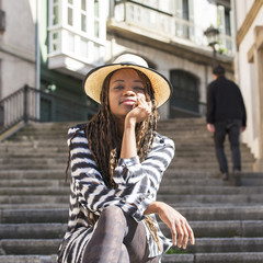 Beautiful african young woman with hat sitting on stairs.