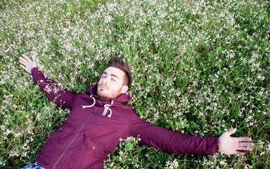 Young man lying on a field of flowers
