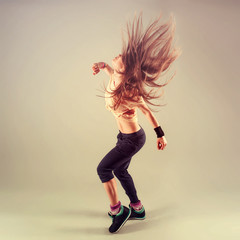 Studio shoot of active female funk jazz dancer moving.