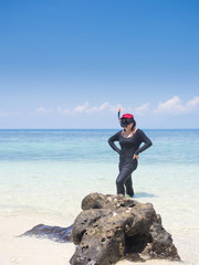 Woman wearing snorkel on summer vacation in tropical sea shore