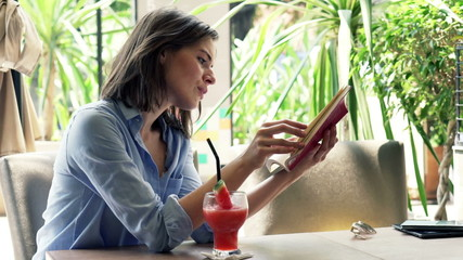 Young, pretty woman reading book sitting in cafe in city