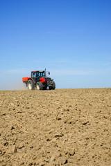Ackerbau - Dünger streuen auf einem weiten Feld, Hochformat