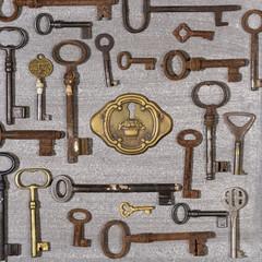 Rusty keys with brass lock on wooden background