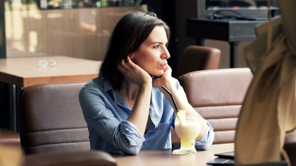 Unhappy, sad woman drinking cocktail sitting in cafe in city