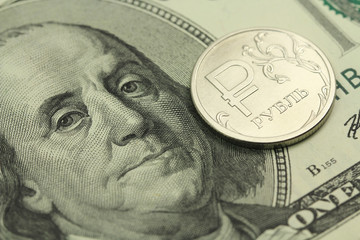 one coin ruble against the background of one hundred dollars