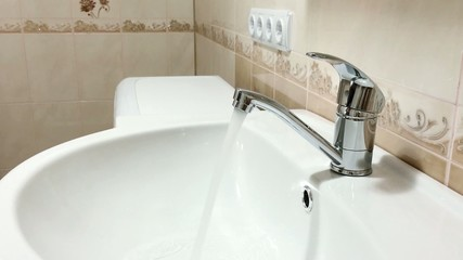 Woman hand opens a water tap in bathroom, then turns water off