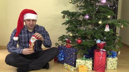 Funny man unfold chocolate Christmas Santa and lick lips