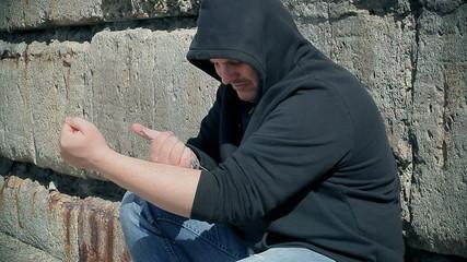 Drug addict man with syringe near hand