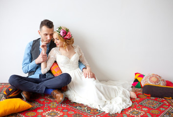 barefooted bride and groom sitting on floor