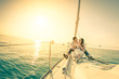 Leinwanddruck Bild - Happy couple in love on sail boat with champagne at sunset