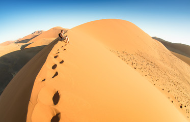 Lonely man sitting on sand at Dune 45 in Sossusvlei