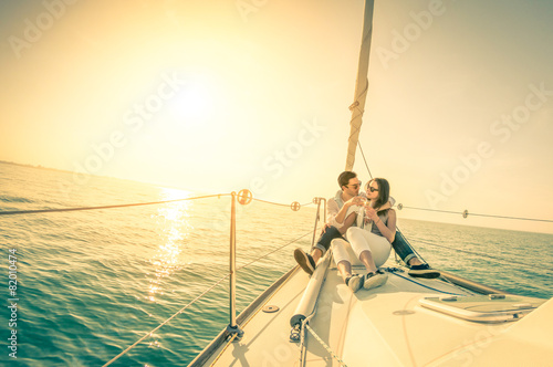 Leinwanddruck Bild Happy couple in love on sail boat with champagne at sunset