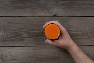 Man holding glass with carrot juice