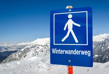 Schild mit Bergpanorama Alpen –Winterwanderweg Winterwandern