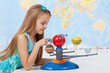 Little girl studies the solar system in geography class
