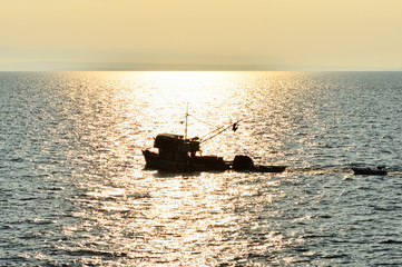 Fischkutter am Meer in untergehender Sonne