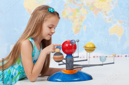 Poster Little girl studies the solar system in geography class