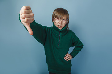 European-looking boy of ten years showing thumbs down on a black