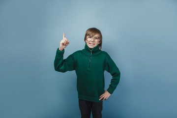 European-looking boy of ten years shows a finger on a gray  back