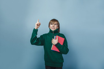 European-looking boy of ten years in glasses holding a book in h